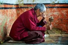 Nonne mit Gebetsmühle versunken im Gebet in Bhutan