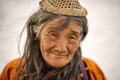 Porträt einer älteren Frau mit Strohhut in Punakha