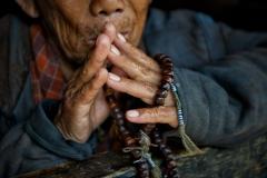 Betende Hände mit Gebetskette in Bhutan