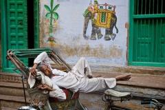 Rikscha-Fahrer macht Pause in Varanasi, Indien