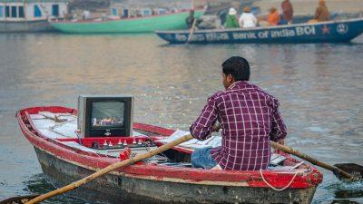 Reisefotografie - Mann mit Fernseher im Boot